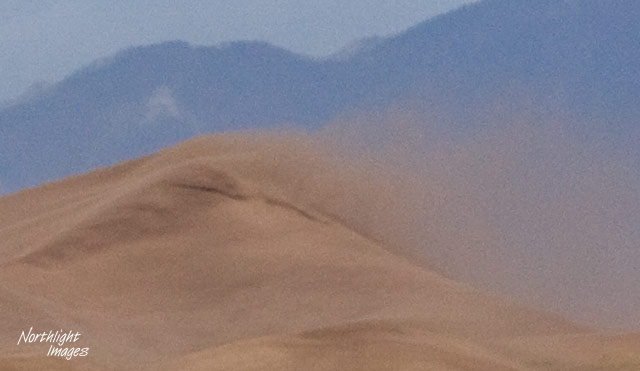 sand blowing over the top of a dune