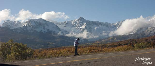 Keith Cooper checking camera in the mountains