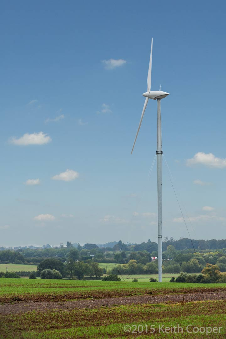 wind turbine in field with clear blue sky