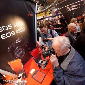 man looking at a camera at a camera show