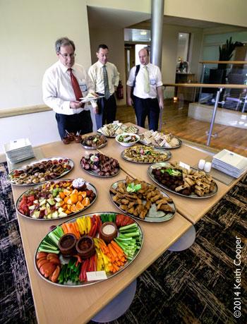 Businessmen standing at buffet lunch