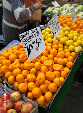 Pile of satsuma oranges on market stall with price ticket
