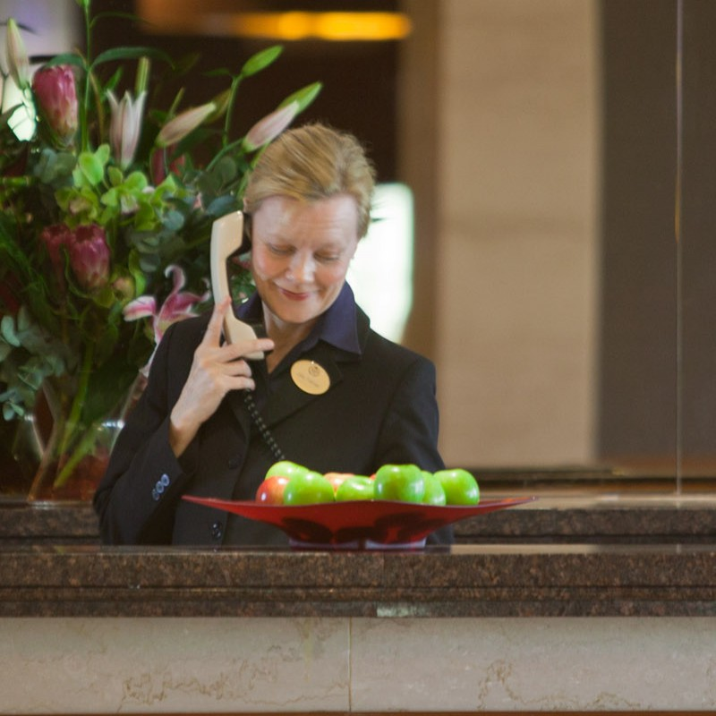 Hotel receptionist answering telephone